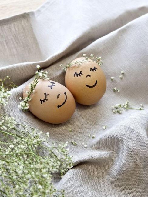 jajeczka wielkanocne z wiankami i uśmiechniętymi twarzami