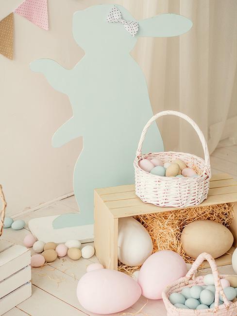 pastelowy papierowy królik za skrynią z iwlkimi pastelowymi jajkami obok niałego koszyka