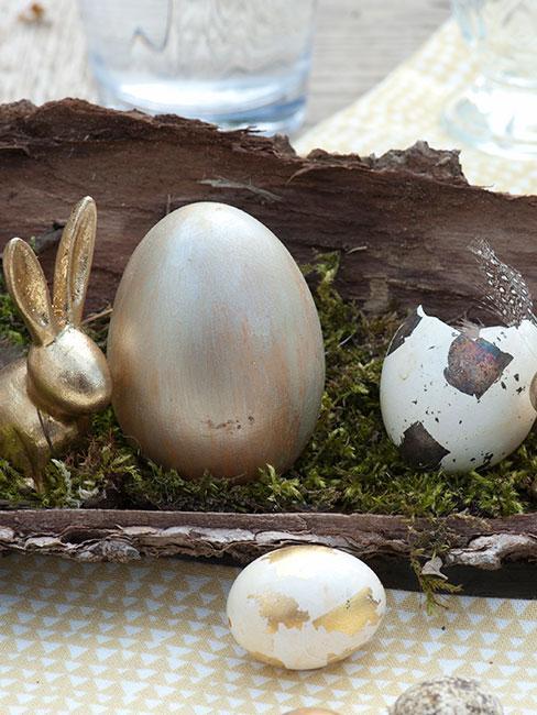 zbliżenie na pozłacane jajko obok złotego królika