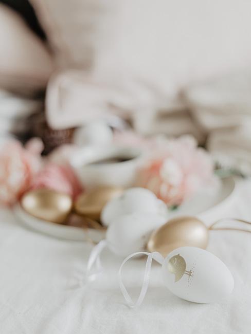 złote i białe jajka wielkanocne na tle różowych kwiatów