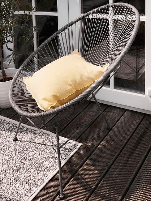 Ażurowy fotel na balkonie z żółtą poduszką