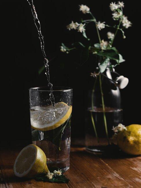 Szklanka z wodą i kawałkiem cytryny, wazon z kwiatami