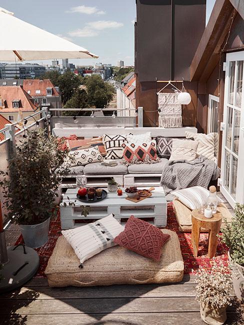 Niewielki balkon w kamienicy z meblami z palet w stylu boho