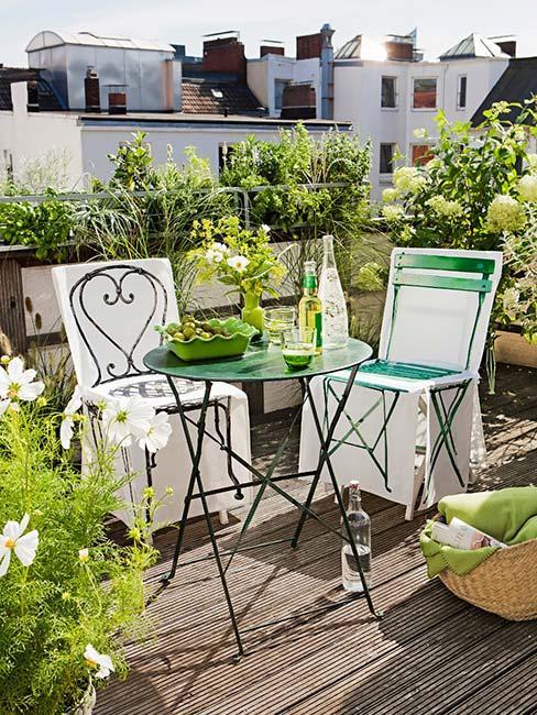 Balkon z metalowymi meblami wśród zieleni