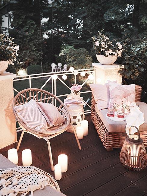 Przytulny balkon óświetlony świeczkami i lampkami z rattanowymi meblami i różowymi poduszkami