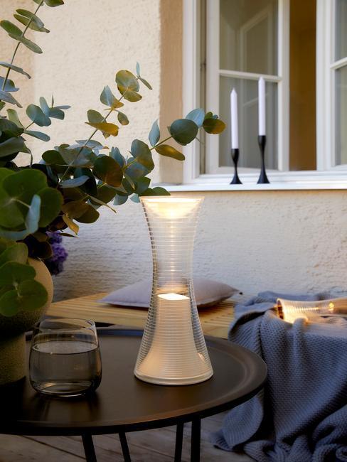 Zbliżenie na stolik z lampą solarną, wazonem oraz ławką w tyle z kocem