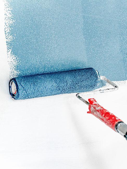Wałek malarski malujący białą ścianę na niebiesko