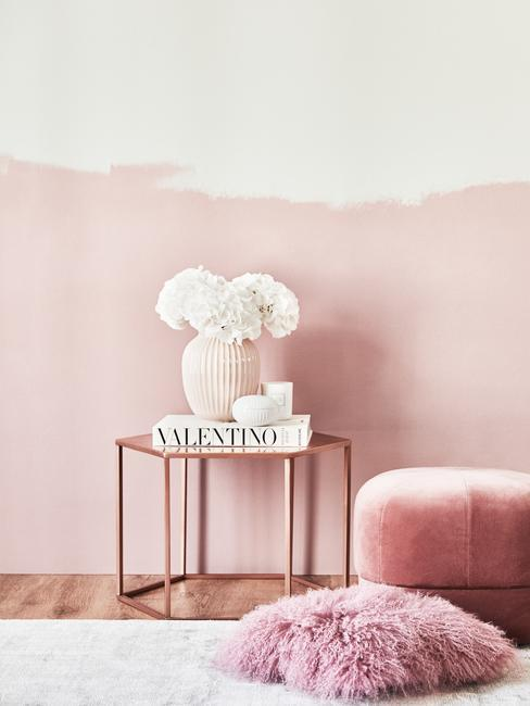 Fragment salonu z różowym pufem, matalowym stolkiem z książką