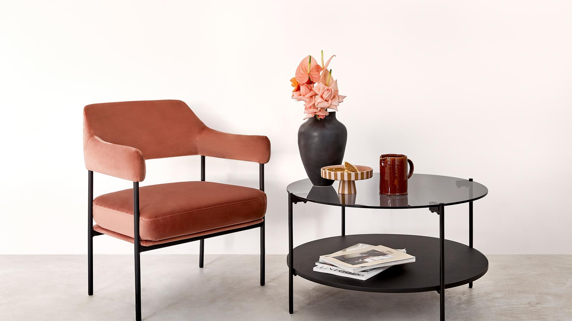 Jasne tło na pulpit z aksamitnym krzesłem w kolorze etrakory obok czarnego stolika kawowego