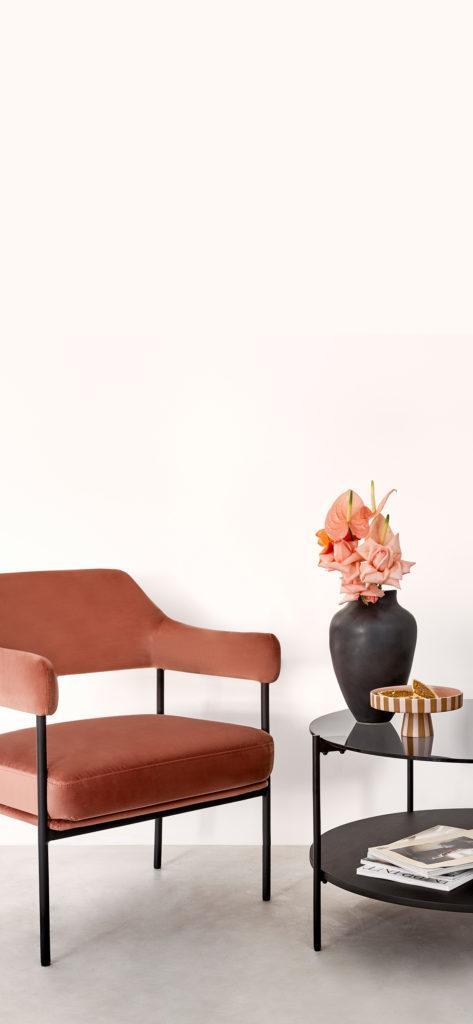 Jasne tło na telefon z aksamitnym krzesłem w kolorze etrakory obok czarnego stolika kawowego