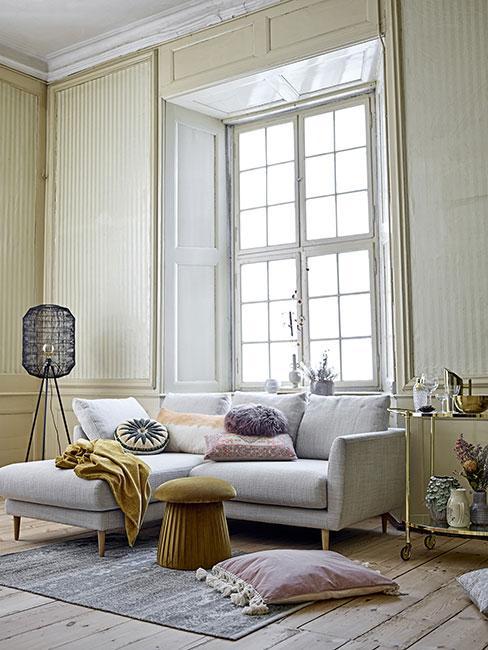 Pastelowy salon w stylu boho w kamienicy z wysokim stropem