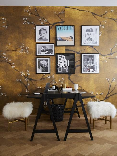Jadalnia z czarnym stołem, stołkami z futrem na tle złotej ściany z japońskim motywem