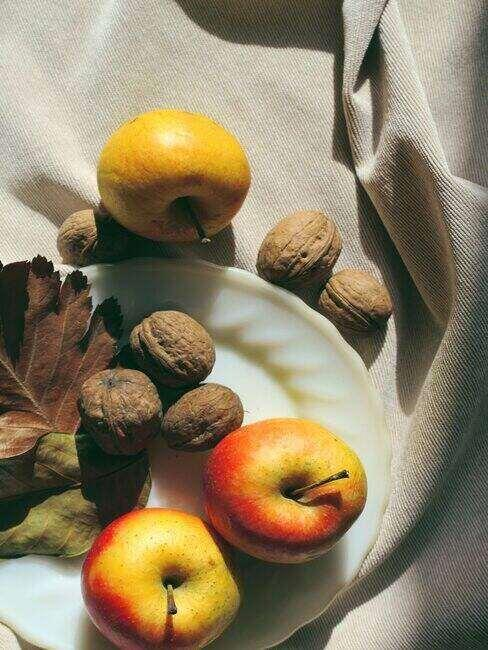 orzechy laskowe i jabłka na talerzu na lnianym obrusie