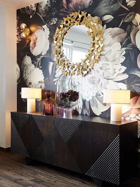 ściana w salonie w stylu glamour z ciemną drewnianą komodą na tle ciemnej fototapety z dużymi kwiatami, na której widniej dekoracyjne kustro słońce