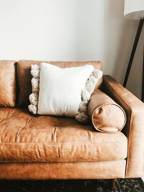 Brązowa kanapa z białą poduszką