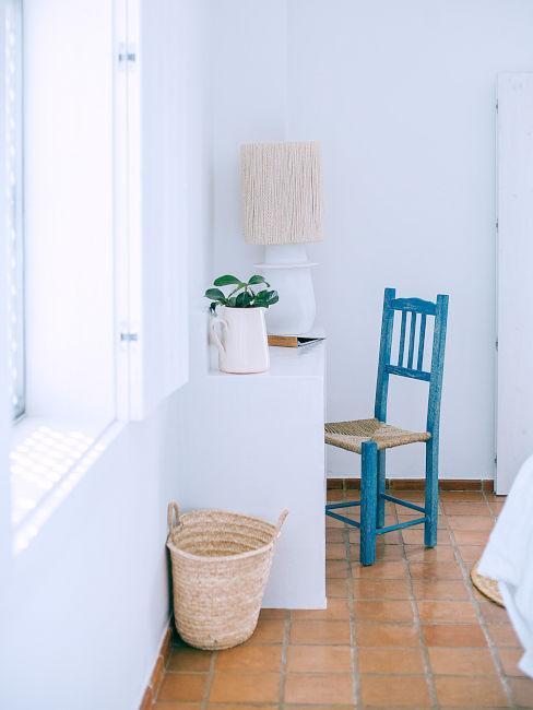Biała konsola przy nienieski drewnianym krześle w białym pomieszczeniu z ceglaną podłogą w stylu greckim