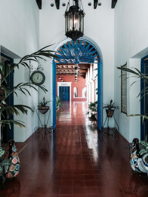 Duży korytarz z podłogą z ciemnej terakoty z łukowymi drzwiami w stylu śródziemnomoeskim