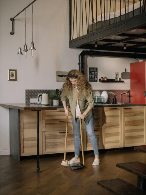 Kobieta zamiatająca podłogę w dużej kuchni w lofcie