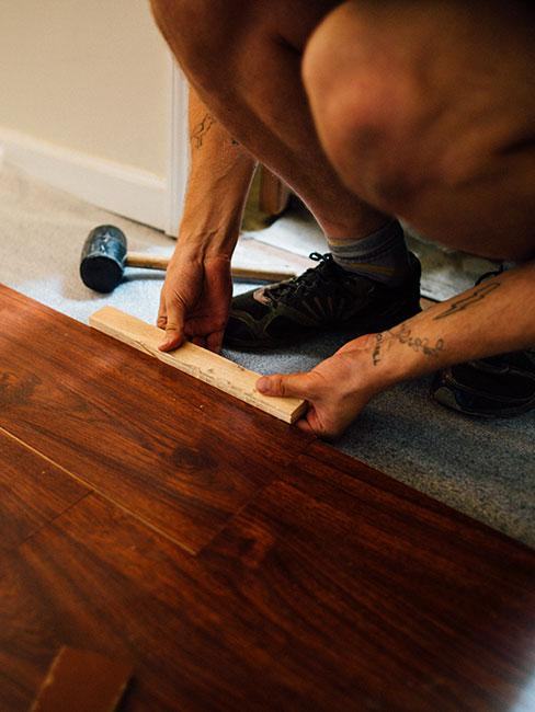 Zbliżenie na ręce układające podłogę