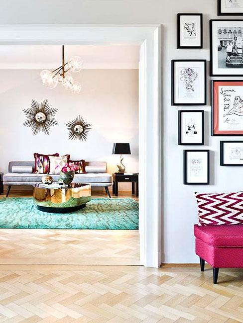 Duże mieszkanie w kamienicy z jasną podłogą z zieloym dywanem i galerią zdjęć w przedpokoju