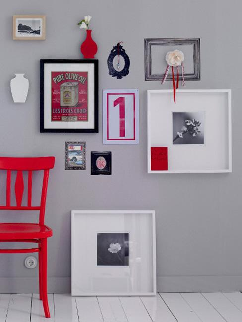 Galeria ścienna obrazów w różnej wielkości na szarej ścine obok czerwonego krzesła