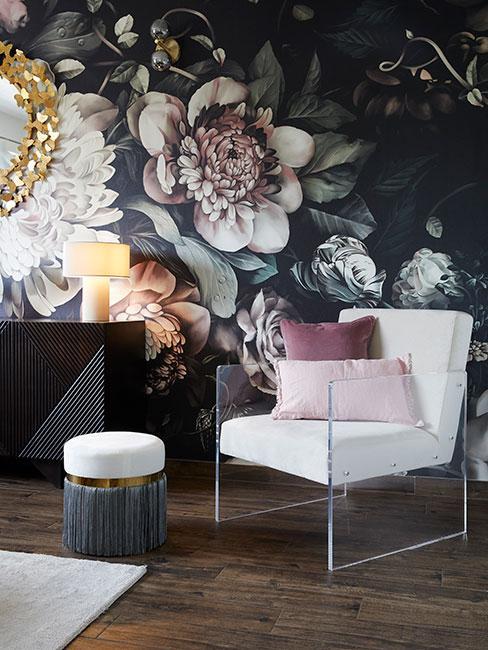Kącik z białym fotelem obok ciemnej drewnianej komody na tle ściany z ciemną tapetą w duże kwiaty
