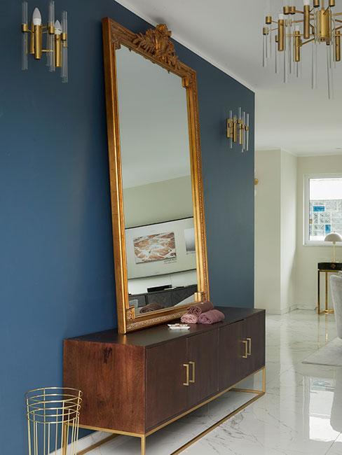 Przedpokój w stylu glamour z dużym barokowym lustrem na tle ciemnoniebieskiej ściany