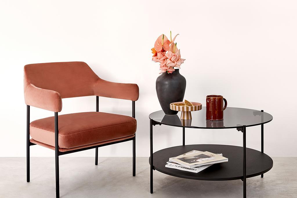 Jasne tło zoom z aksamitnym krzesłem w kolorze etrakory obok czarnego stolika kawowego