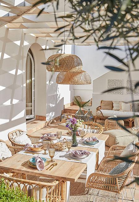 Słoneczny taras ze stołem drewnianym, ażurowymi meblami i lampami w stylu śródziemnomorskim