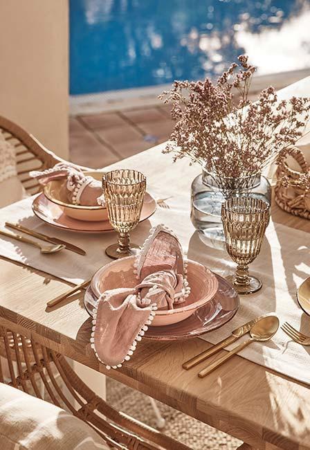 Stół na tarasie z różowymi talerzami w stylu boho