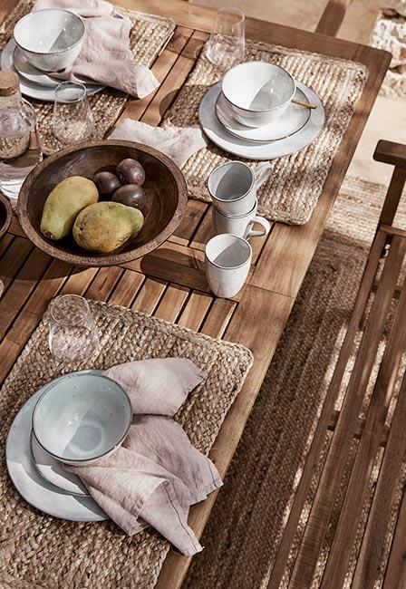 Stół na tarasie z zastawą z kamionki, linianymi serwetkami i podkładkami z juty