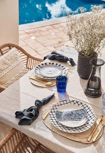 stół na słonecznym zastawiony białoniebieskimi talerzami, złotymi sztućcami i niebieskimi skzklankami