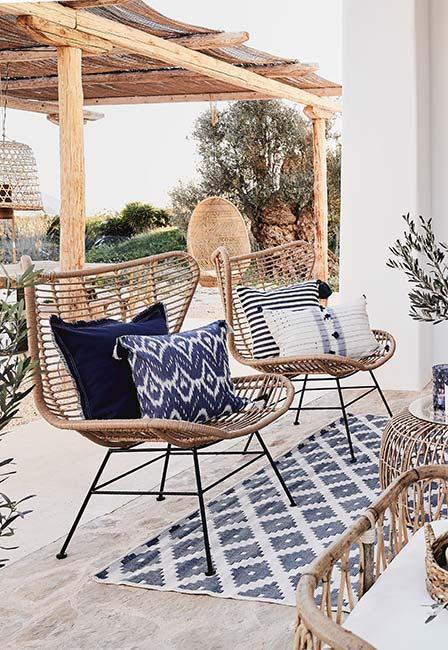 śródziemnomorski taras z jasnobrązowymi ażurowami meblami i niebieskimi tekstyliami w greckim stylu