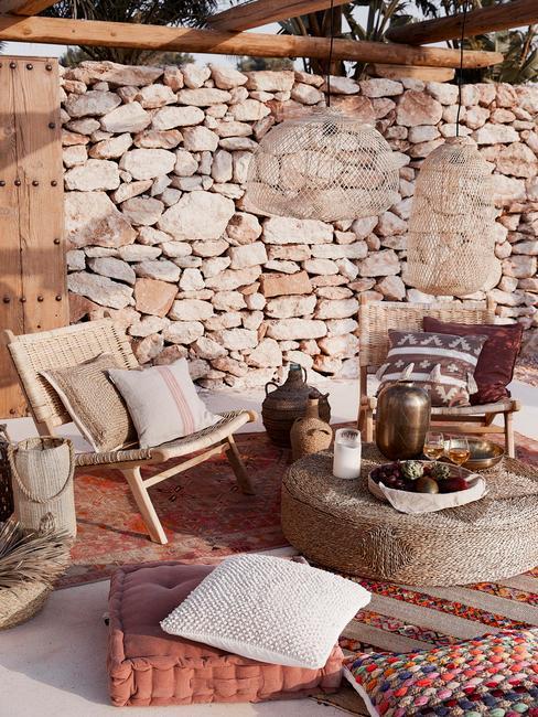 Taras w stylu boho ze ścianą z kamienia i beżowymi meblami z bambusa i juty