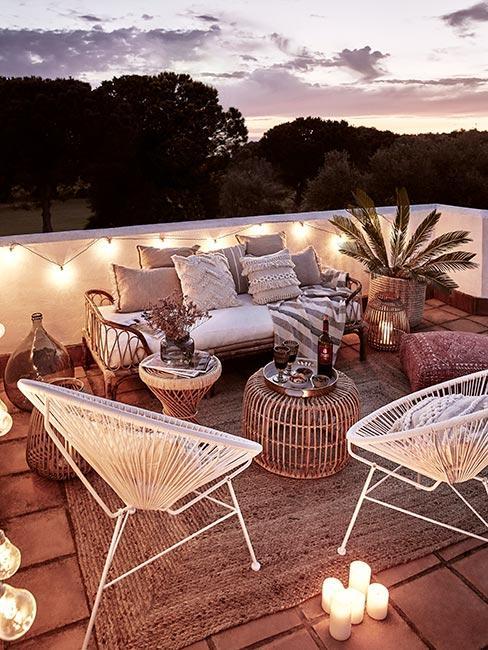 Taras śródziemnomorski z białymi ażurowymi fotelami oświetlony lampkami
