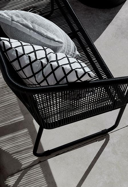 zbliżenie na czraną ażurową kanapę zewnętrzną i monochromatyczne poduszki