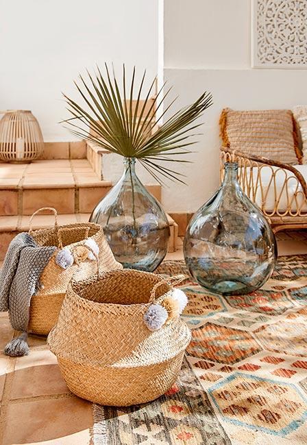 Dwa duże wazony podłogowe na tarasie obok kosza z trawy morskiej