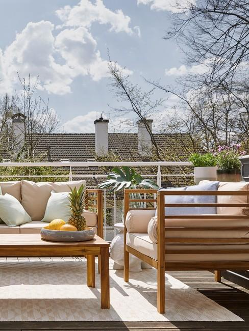 Drewniana sofa oraz krzesło z poduszkami na tarasie na dachu budynku