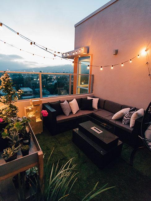 Duży balkon w bloku z narożna sofą zewnętrzną i sztuczną trawą