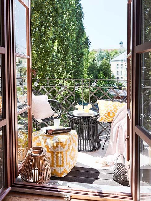 Mały balkon z czarnymi ażurowymi meblami i żółtą pufą