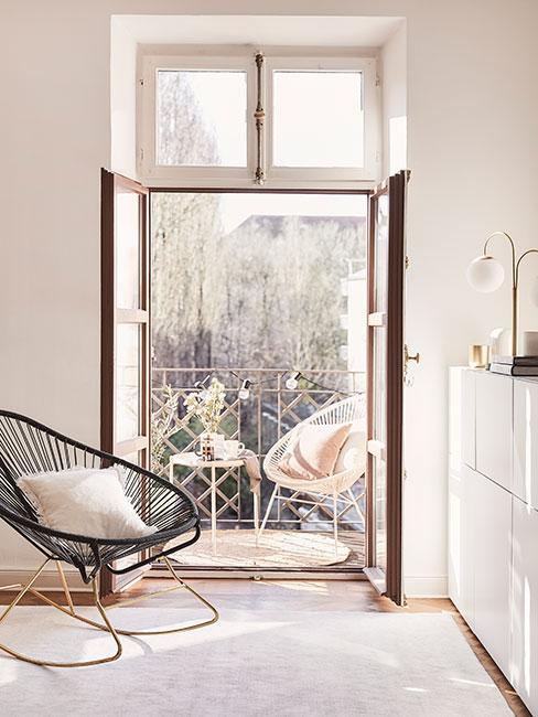 Mały miejski balkon z dużym fotelem na płozach w salonie