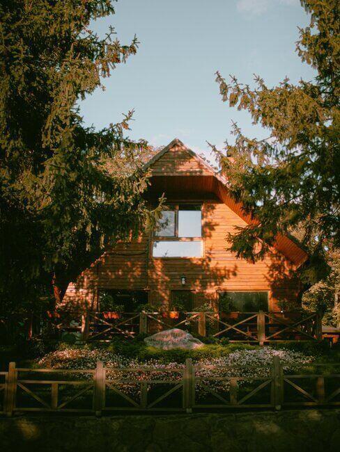 Drewniany domek oświetlony zachodzącym słońcem, otoczony drzewami