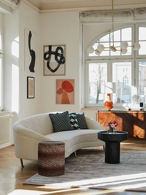 salon w stylu retro z beżową sofą nerką i zielonymi poduszkami