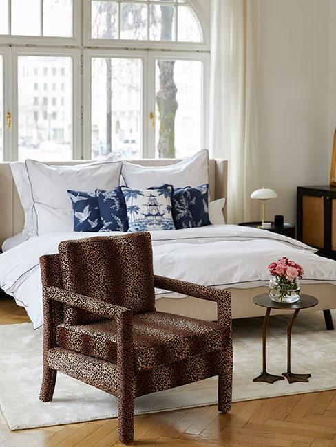 Łóżko z niebieskimi poduszkami z chińskim motywem obok fotelu w panterkę
