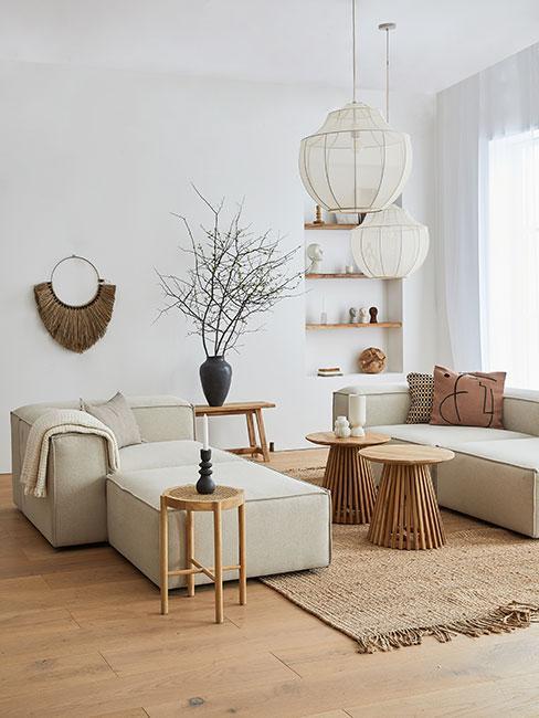 Salon z beżową sofą modułową i brązowymi dekoracjami i stolikami w stylu boho