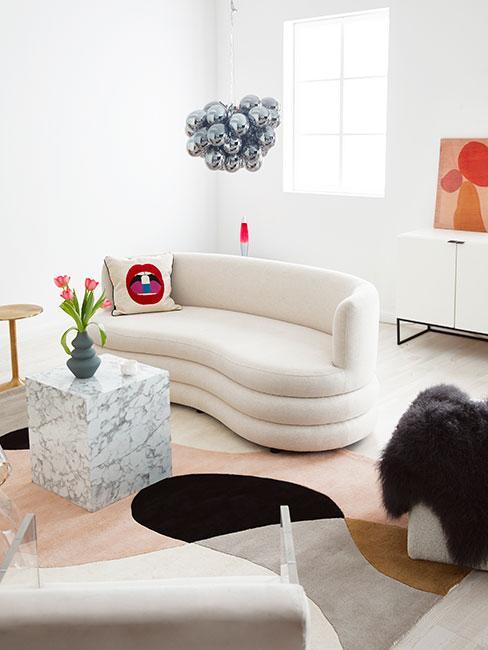 Salon w stylu eklektycznym z beżową sofą nerką boucle, marmeurowym stolikiem i srebrną lampą wiszącą