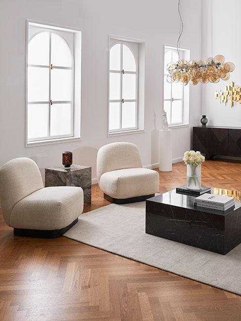Salon z dwoma nowoczesnymi fotelami boucle, czarnym stolikkiem z marmuru