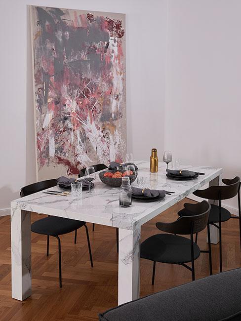 Jadalnia z dużym stołem z białego marmuru, czarnymi krzesłami z aksamitu i dużym abstrakcyjnym obrazem