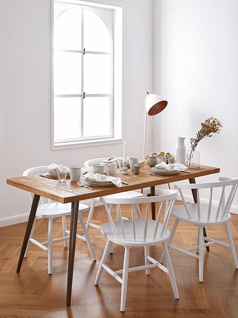Jadalnia w stylu skandynawskim z białymi krzesłami, brązowym stołem z drewna i białą lampą podłogową