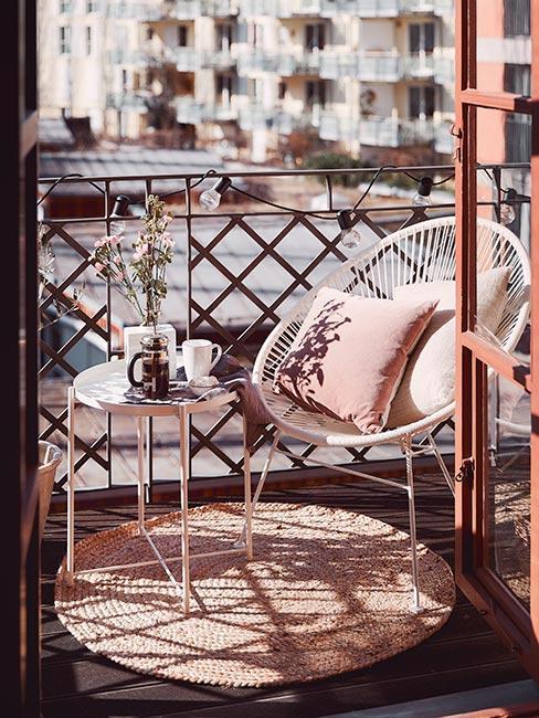 Mały miejski balkon z białym ażurowym fotelem i białym metalowym stolikiem